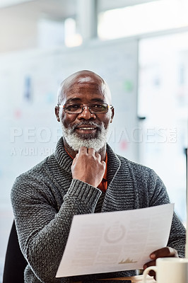 Buy stock photo Portrait of a mature businessman going through paperwork in an office