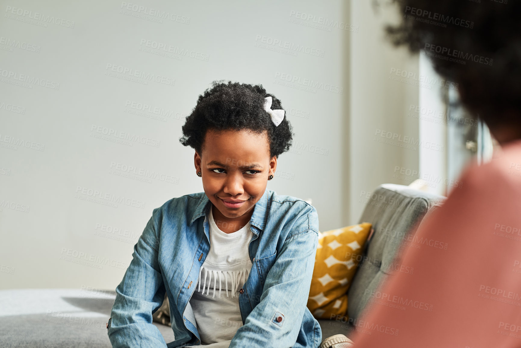 Buy stock photo Cropped shot of a young girl looking upset while being scolded by her mother