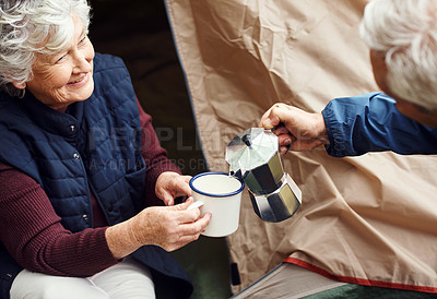 Buy stock photo Shot of a senior couple drinking coffee while camping in the wilderness