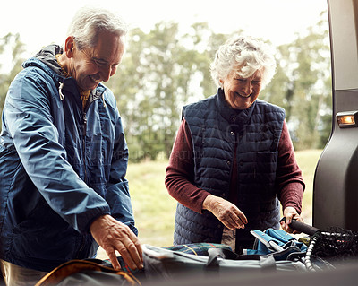 Buy stock photo Shot of a senior couple unpacking camping equipment from their vehicle in the wilderness
