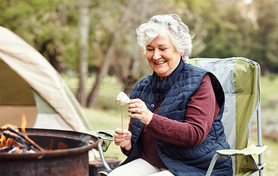 Buy stock photo Shot of a senior woman roasting marshmallows while camping in the wilderness