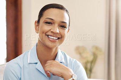 Buy stock photo Cropped portrait of an attractive young nurse wearing her uniform and sitting alone on the sofa in a nursing home