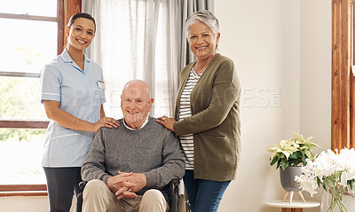 Buy stock photo Portrait of an attractive young female nurse standing next to an elderly male tenant in a wheelchair and his wife at an old age home