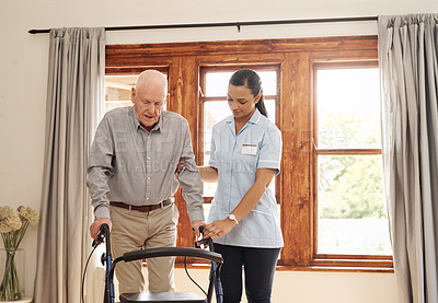 Buy stock photo Cropped shot of an attractive young female nurse assisting an elderly man with a walking frame inside of an old age home
