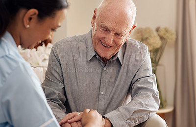 Buy stock photo Cropped shot of an attractive young nurse sitting with her senior patient in the living room of his nursing home