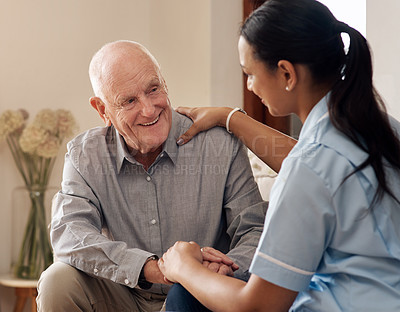 Buy stock photo Cropped shot of an attractive young nurse sitting and comforting a senior patient in the living room of his home