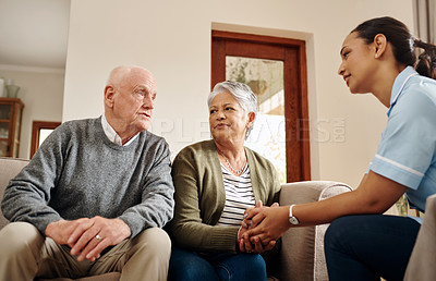 Buy stock photo Cropped shot of an attractive young nurse sitting and bonding with her senior patients in the living room at home