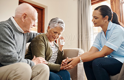 Buy stock photo Cropped shot of an affectionate senior man comforting his crying wife while sitting with their nurse aid at home
