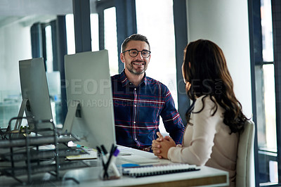 Buy stock photo Cropped shot of a handsome mature businessman sitting and talking with his female colleague in the office