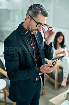 Buy stock photo Cropped shot of a handsome mature businessman standing and using a cellphone while his female colleague sits behind him