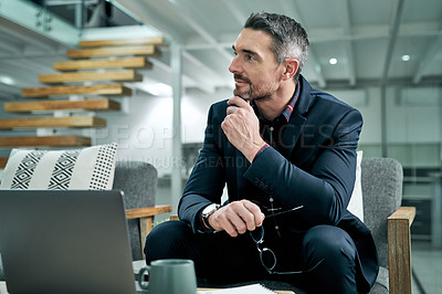 Buy stock photo Cropped shot of a handsome mature businessman sitting alone in his office and looking away while working on his laptop