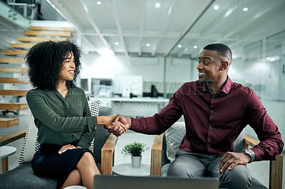 Buy stock photo Cropped shot of two young business colleagues sitting in the office together and shaking hands before a meeting