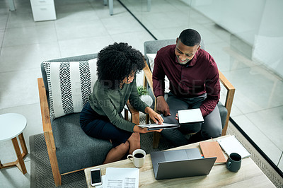 Buy stock photo High angle shot of two young businesspeople sitting in the office and having a discussion while working on a tablet