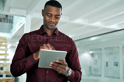 Buy stock photo Cropped shot of a handsome young businessman standing alone in his office and using a tablet