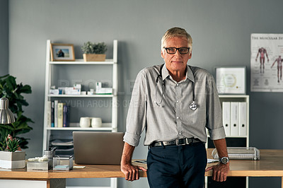 Buy stock photo Cropped portrait of a handsome mature male doctor standing in his office