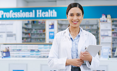 Buy stock photo Portrait of a young pharmacist holding a digital tablet while standing in a chemist