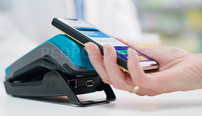 Buy stock photo Closeup shot of a customer making a payment with her cellphone using NFC technology in a pharmacy
