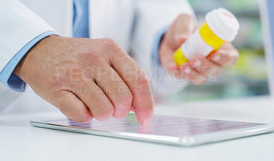Buy stock photo Closeup shot of a pharmacist using a digital tablet while holding a bottle of medication in a chemist