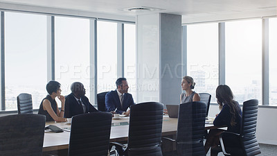 Buy stock photo Cropped shot of a diverse group of businesspeople sitting together around a boardroom table and having a meeting