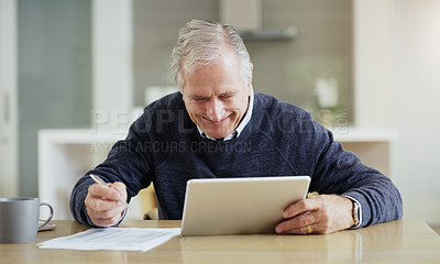 Buy stock photo Shot of a senior man using a digital tablet while going over his bills and finances at home