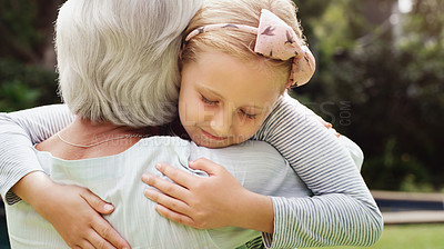 Buy stock photo Shot of an adorable little girl warmly hugging her grandmother outdoors