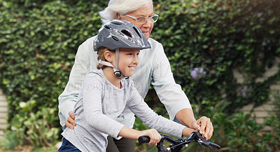 Buy stock photo Shot of a grandmother teaching her granddaughter how to ride a bicycle outdoors