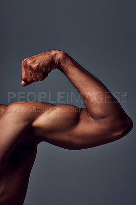 Buy stock photo Studio shot of an unrecognizable muscular sportsman flexing his bicep against a grey background