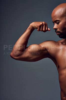 Buy stock photo Studio shot of a muscular shirtless young sportsman flexing his bicep against a grey background