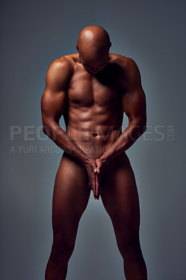 Buy stock photo Studio shot of a muscular young man posing nude with his hands joined together on his manhood against a grey background