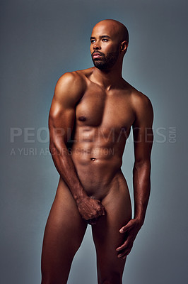 Buy stock photo Studio shot of a muscular young man posing nude with his hand covering his manhood against a grey background