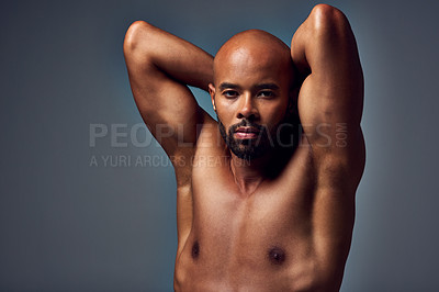 Buy stock photo Studio portrait of a muscular young man posing shirtless with his hands behind his head against a grey background
