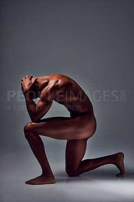 Buy stock photo Studio shot of a muscular young man posing nude on one knee against a grey background
