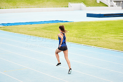 Buy stock photo Rearview shot of an unrecognizable young female athlete running along the track