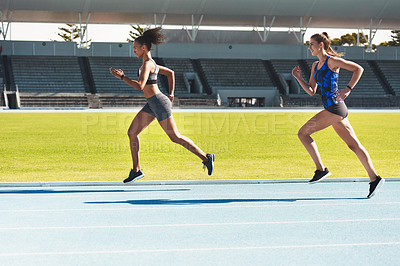 Buy stock photo Full length shot of two attractive young female athletes running along the track