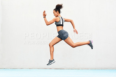 Buy stock photo Full length shot of an attractive young female athlete running along the track