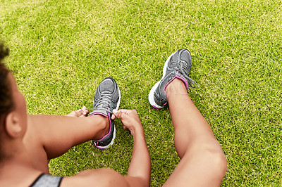 Buy stock photo High angle shot of an unrecognizable young female athlete fastening her laces while working out at the track