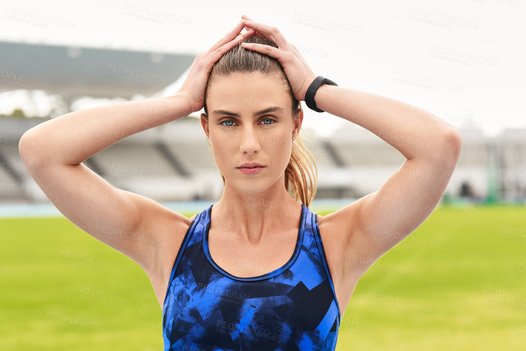 Buy stock photo Cropped portrait of an attractive young female athlete standing with her hands on her head on the track
