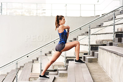 Buy stock photo Full length shot of an attractive young female athlete working out on a flight of stairs at the track
