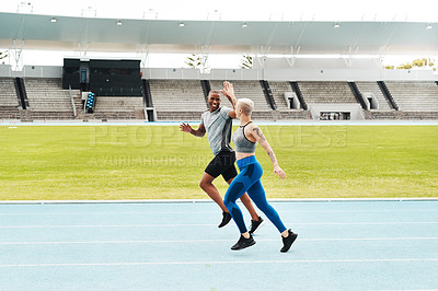 Buy stock photo Full length shot of two young athletes giving each other a high five during a run on a track field