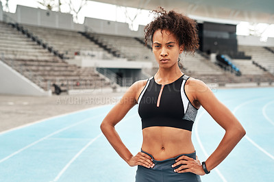 Buy stock photo Cropped portrait of an attractive young athlete standing akimbo after an outdoor track and field training session alone