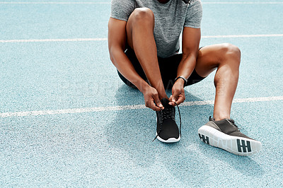 Buy stock photo Cropped shot of an unrecognizable athlete sitting and tying his shoelaces before going for a run alone