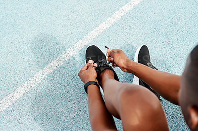 Buy stock photo Cropped shot of an unrecognizable athlete crouching down and tying his shoelaces before going for a run alone