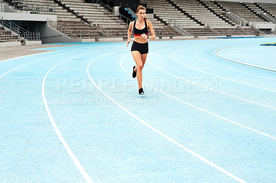 Buy stock photo Full length shot of an attractive young athlete running a track field alone during a workout session outdoors