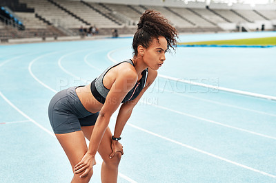Buy stock photo Cropped shot of an attractive young athlete standing on a track field alone and catching her breath after running