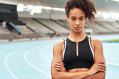Buy stock photo Cropped portrait of an attractive young athlete standing alone with her arms folded before running a track field
