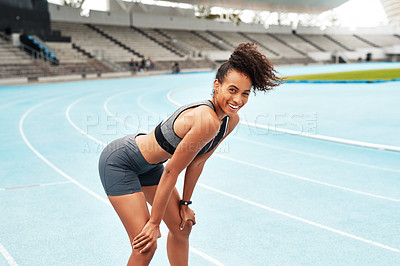Buy stock photo Cropped portrait of an attractive young athlete standing on a track field alone and catching her breath after running