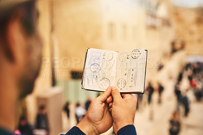 Buy stock photo Cropped shot of an unrecognizable man holding a passport while sightseeing in a foreign city