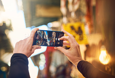 Buy stock photo Cropped shot of a woman taking pictures with her smartphone while exploring a marketplace in Israel