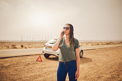 Buy stock photo Shot of a young woman standing next to her broken down vehicle and using a smartphone