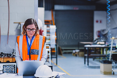 Buy stock photo Cropped shot of a focused female engineer working on a laptop inside of a workshop